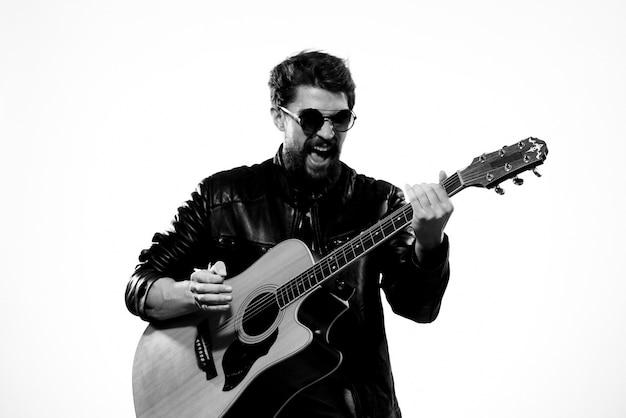 Мужчина играет на гитаре в черной кожаной куртке с очками на светлой стене