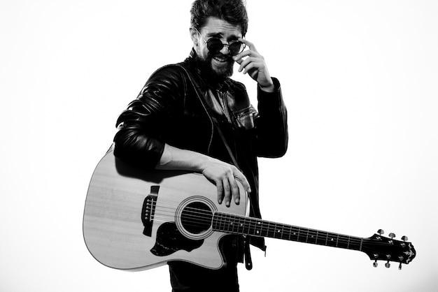 男は黒い革のジャケットでギターを弾く