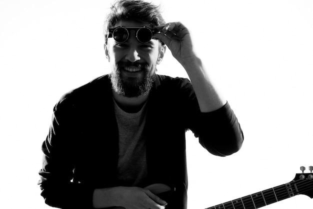 男は黒い革でギターを弾く