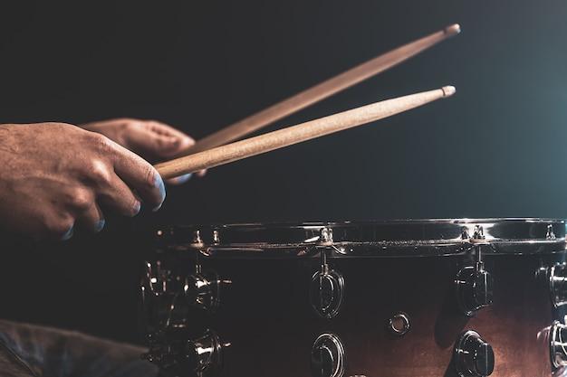 男は太鼓の棒で演奏し、ドラマーは打楽器をクローズアップで演奏します。