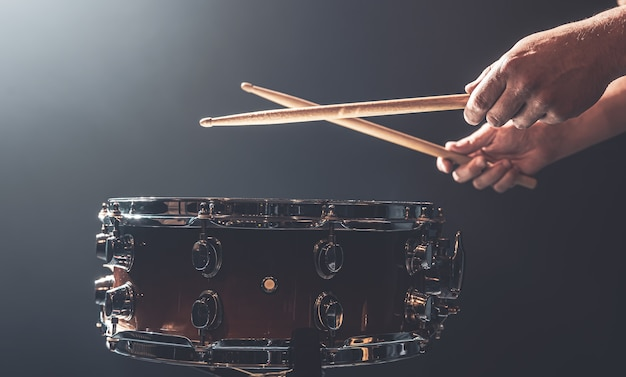 남자는 드럼에 막대기를 가지고 놀고, 드러머는 타악기를 연주하고, 공간을 복사합니다.