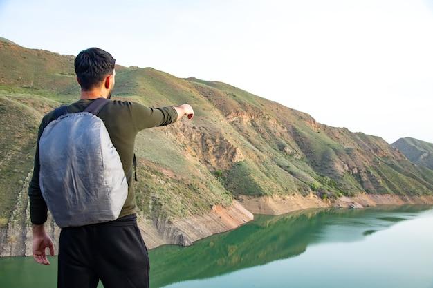 男は湖のほとりの崖の上のポイントを指しています