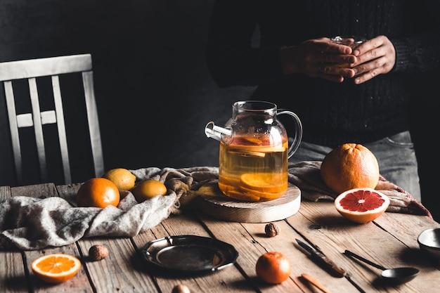男は木製のテーブルに柑橘系のお茶を注ぐ。ヘルシードリンク、ヴィンテージスタイル。ビーガン、エコ製品。