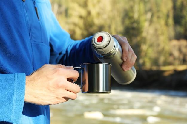 男は魔法瓶から森のカップにコーヒーを注ぐ