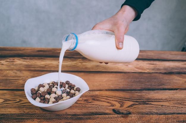 Мужчина наливает молоко в кукурузные хлопья на деревянном.