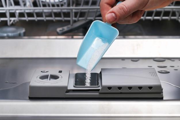 Мужчина насыпает в посудомоечную машину порошок для мытья посуды.