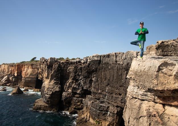 Мужчина занимается йогой. поза дерева на краю обрыва над морем. понятие свободы, здоровья и гибкости.