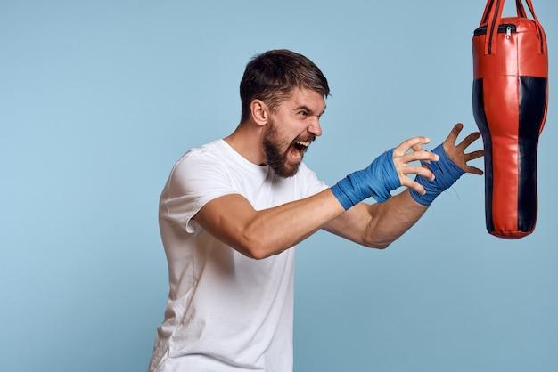 Мужчина практикует удар на боксерской груши в белой футболке на синем фоне.