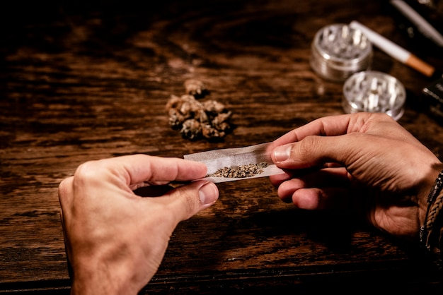 Мужчина руками скручивает косяк марихуаны из дымящейся бумаги.