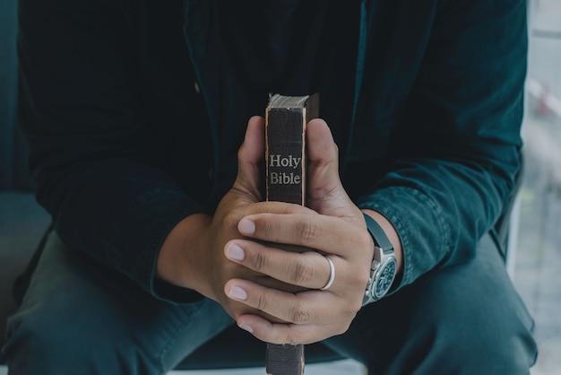 Мужчина молится с библией и молится в спальне религия молится образование