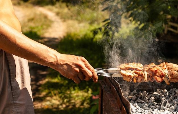 男がグリルで美味しいバーベキューポーク串を作る