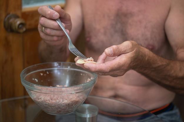 男はひき肉で餃子を準備します。