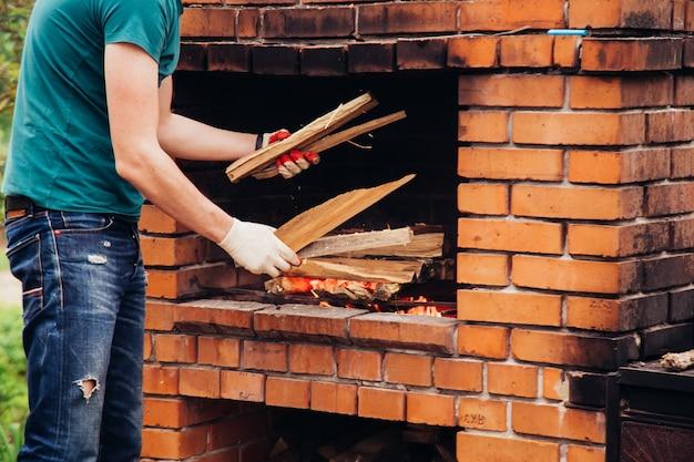 男は休暇や週末に屋外のピクニックでバーベキューグリルでステーキを準備します