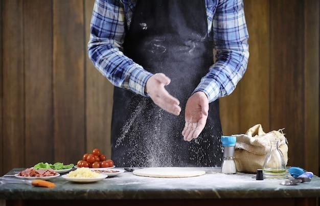 Мужчина готовит пиццу, замешивает тесто и кладет ингредиенты