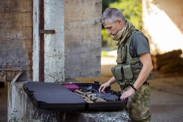 軍服でエアガンゲームの準備をしている男