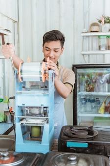 한 남자가 밀봉 기계로 음료를 눌렀다.