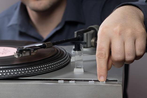 男が蓄音機のビニールレコードプレーヤーのボタンを押す。
