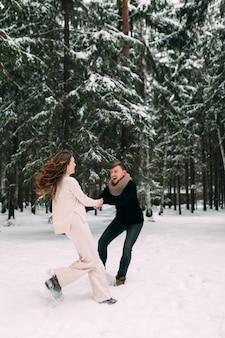 Мужчина тянет за собой женщину в заснеженном лесу и улыбается