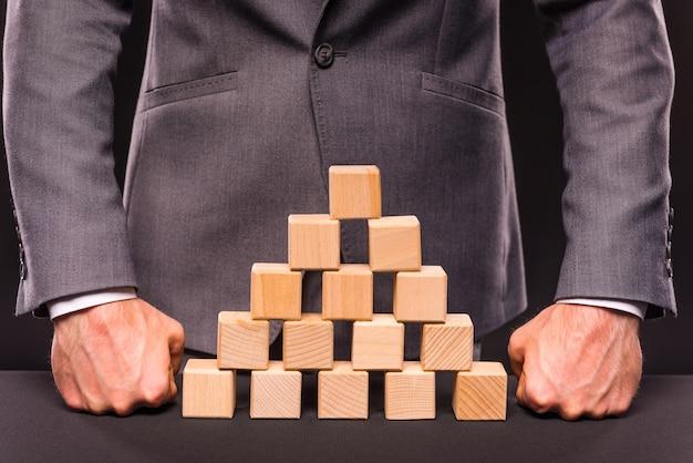 Человек кладет кубики в пирамиду, стоящую над ними.