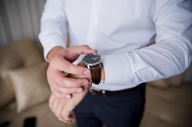 Мужчина надевает на руку классические часы