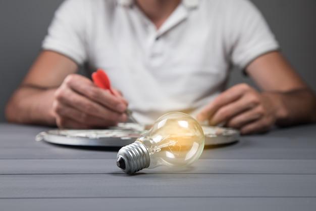 한 남자가 다트 보드 중앙에 다트를 놓고 테이블 위에 전구를 놓습니다. 개념 아이디어 및 목표