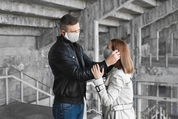 男性が女性の顔に防護マスクを付けます。コロナウイルス、コビッド-19