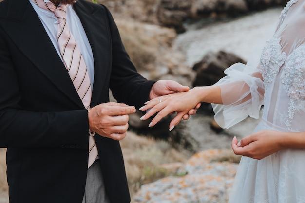 Мужчина надевает кольцо на палец женщины Premium Фотографии