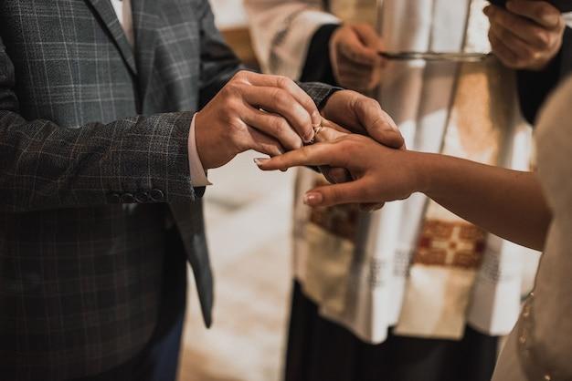 Мужчина надевает обручальное кольцо на руку женщины