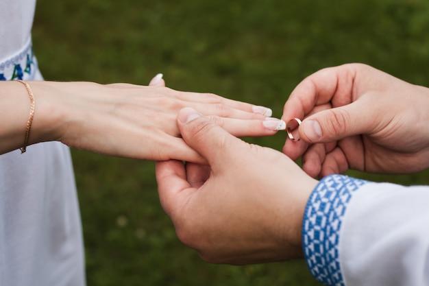 한 남자가 여자에게 결혼 반지를 낀다.
