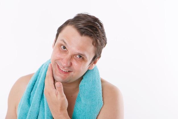 男は彼の顔にアフターシェーブを置きます。男は顔を撫でます。バスルームでの朝のトリートメント。コピースペース