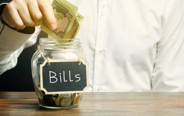 남자는 청구서 유틸리티 청구서 지불 개념이라는 단어로 유리 항아리에 돈을 넣습니다.