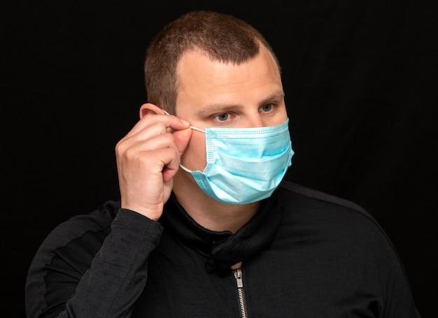 Мужчина надевает медицинскую маску на лицо, инструкция о том, как носить маску