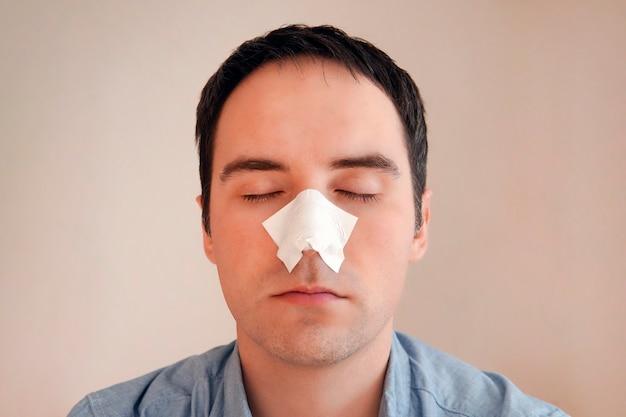 男性が黒い点から鼻のストリップを付けたり外したりします。にきびや面皰からの石炭洗浄ストリップ。パーソナルケアの概念。