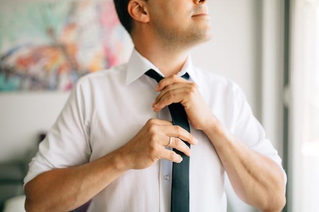 Мужчина надевает и завязывает галстук во время подготовки к свадебной церемонии