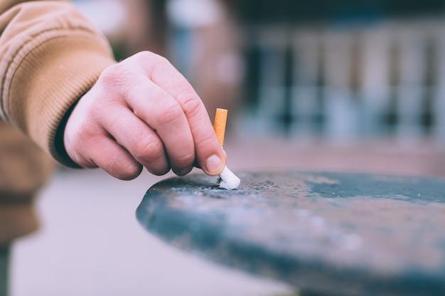 Мужчина тушит сигарету в мусорном ведре.
