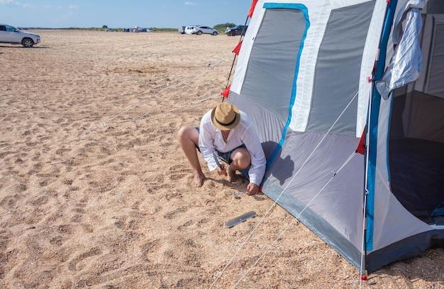 한 남자가 텐트 도시에 텐트를 세웁니다. 여름 야외 레크리에이션.