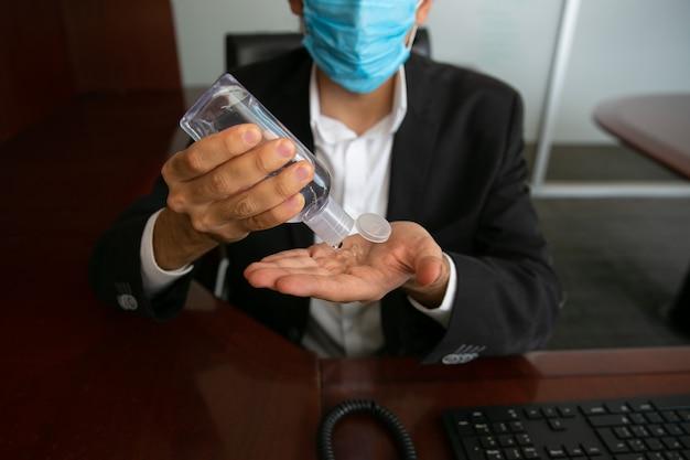 항균 젤을 바르는 남자 그는 바이러스 예방을 위해 보호 마스크를 쓰고있다