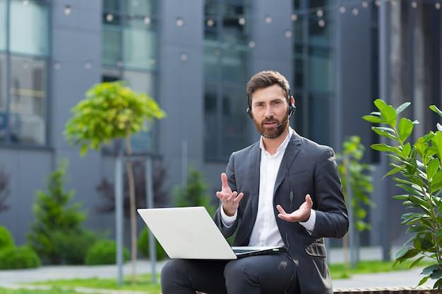 Мужчина ссорится и расстроен, разговаривает на видео, используя ноутбук и гарнитуру с микрофоном, сердитый сторонник сидит в общественном месте возле офисного центра