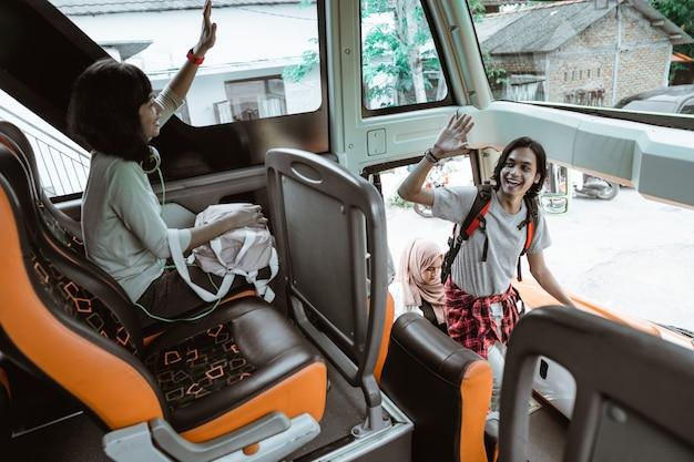 バスに乗り込むと、男が手を挙げて友達に挨拶した。