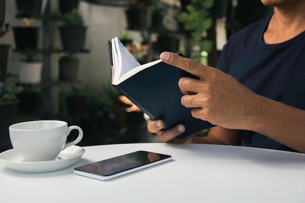 Мужчина читает книгу с чашкой кофе. человек сидит в кресле у себя дома, читает книгу и расслабляется.