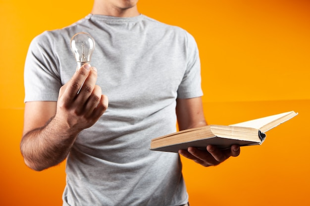 Мужчина читает книгу и держит лампочку. концептуальная идея из книги о оранжевом офисе