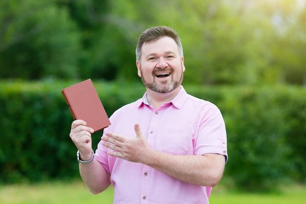 男は公園の路上で良い本を売ることを勧めます