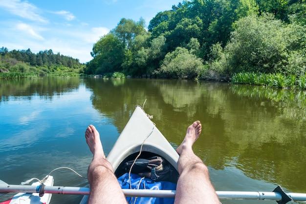강에서 카약에서 휴식을 취하는 남자. 푸른 물과 푸른 나무가 있는 풍경
