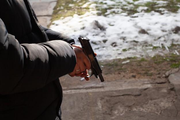 男が銃をリロードします。冬、戸外、射撃場