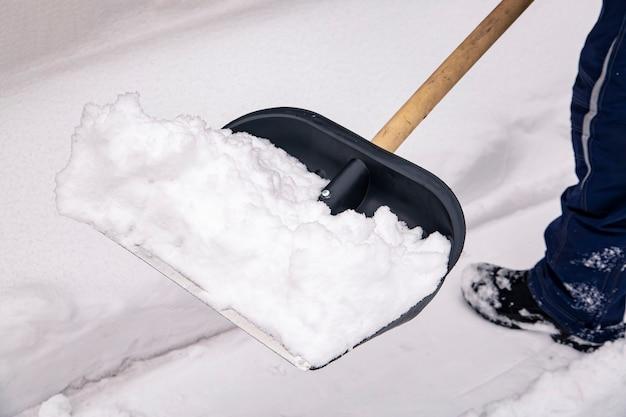 男はシャベルで雪を取り除きます。季節の仕事。
