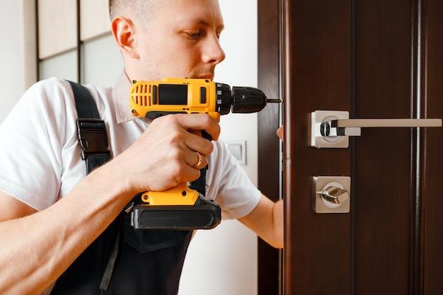 Мужчина ремонтирует дверную ручку. разнорабочий ремонт дверного замка в комнате