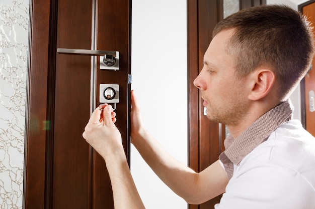 Мужчина ремонтирует дверную ручку
