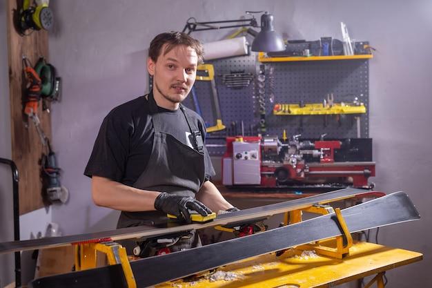 Ремонтник человек в мастерской лыжного сервиса ремонтирует лыжи