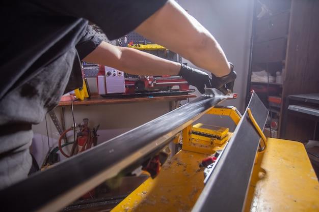スキーを修理するワークショップスキーサービスの男性修理工