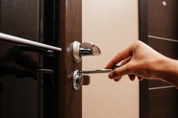 한 남자가 드라이버로 방 문 자물쇠를 수리합니다.